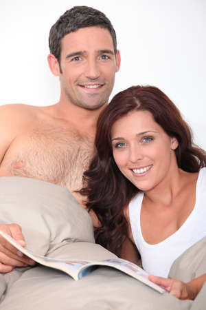 hairy chest: Couple reading a book in bed Stock Photo