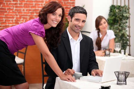 proprietor: Woman leaning over a man in a restaurant with other diners in the background