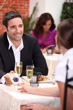dinner wear: Man giving partner a gift Stock Photo