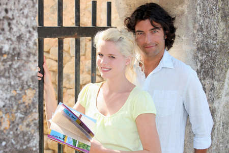 couple near an iron gate and old stone walls, the woman is holding a guidebook photo