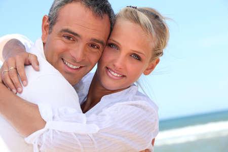 honey blonde: Embracing on the beach Stock Photo