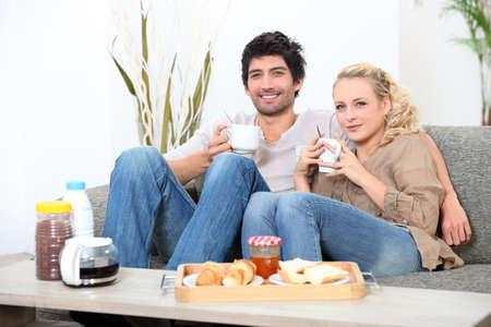 buen vivir: pareja de tener el desayuno en el sofá Foto de archivo