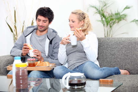 knees bent: Couple having breakfast on the couch Stock Photo