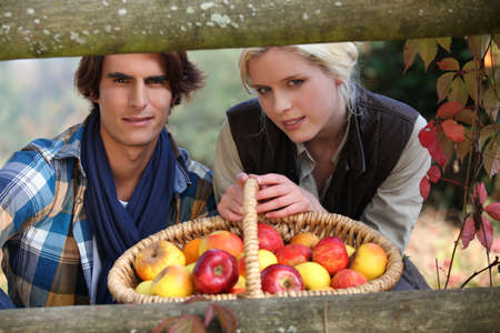 a young couple posing behind a wooden barrier with a wickerwork basket full of apples photo
