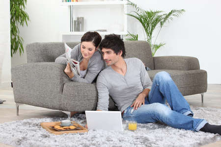 lying on couch: Couple taking breakfast. Stock Photo