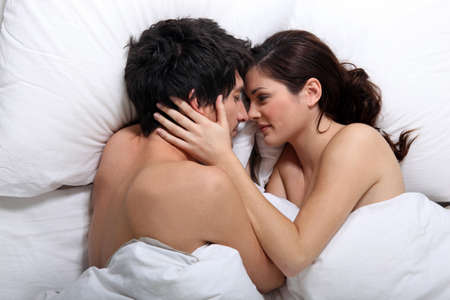sexy woman on bed: Affectionate couple kissing in bed