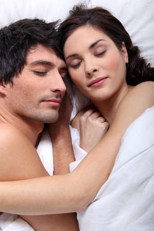 snuggling: Couple snuggling in bed together
