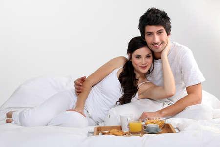 couple having breakfast in bed photo