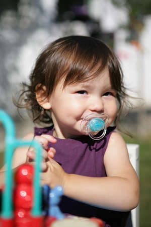 endearment: Little girl with dummy at at the playground
