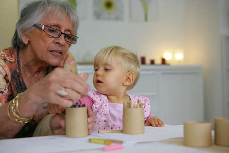 upbringing: Young child coloring with grandma Stock Photo