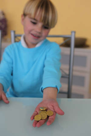Little boy holding coins photo
