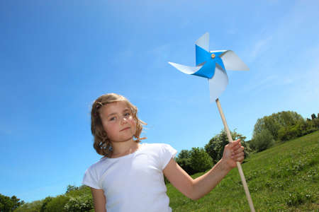 Little girl stood with toy wind mill photo