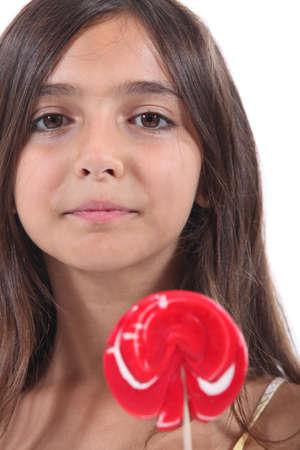 sucking: little girl licking a lollipop