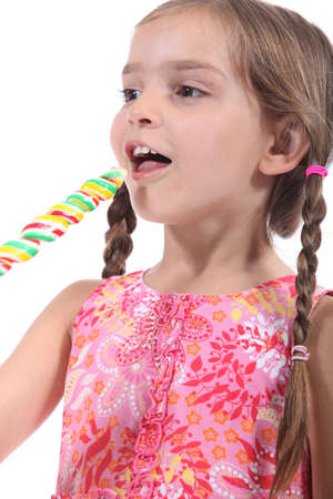 Little girl with multicolored lollipop photo