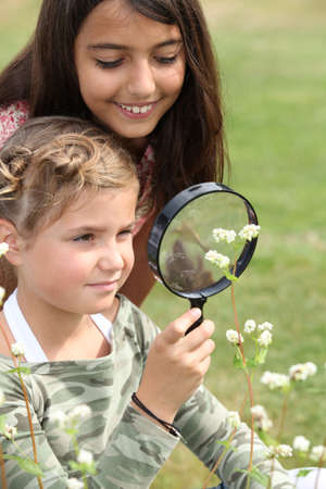 Girls looking through magnifying glass