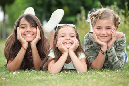 supported: Girls lying on grass Stock Photo