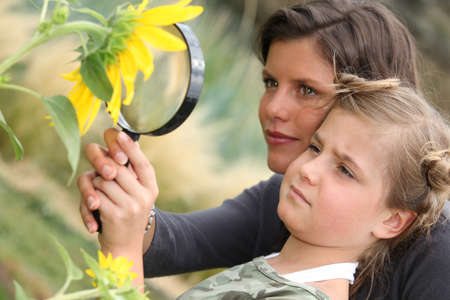 outside of the country: Mother and daughter examining a sunflower through a magnifying glass