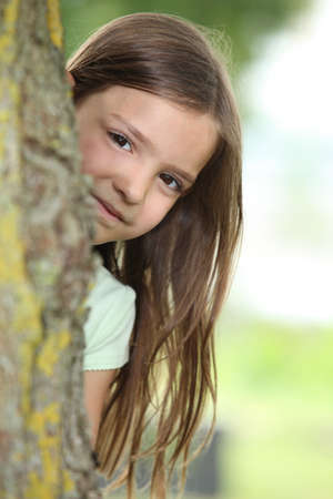 Little girl behind a tree photo