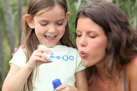 ear rings: Mom and girl making soap bubbles