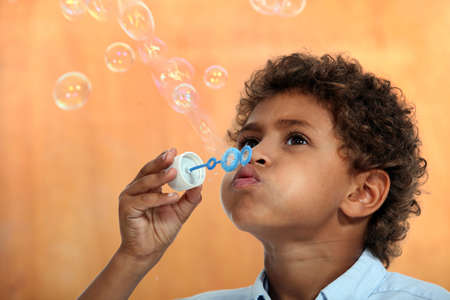 cute mixed-race little boy blowing soap bubbles photo