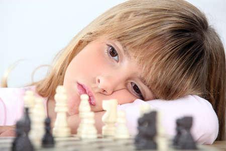 impassive: Bored girl playing chess