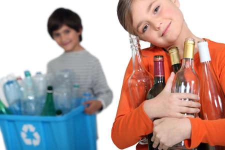 household waste: Kids recycling glass bottles