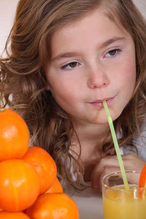 suck: Little girl drinking orange juice through straw Stock Photo