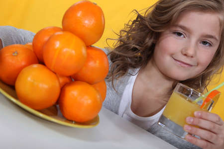 Little girl with glass of orange juice photo