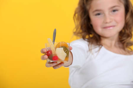 Little girl with fruit salad photo