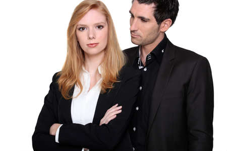 convinced: a business woman with crossed-arms and her colleague Stock Photo