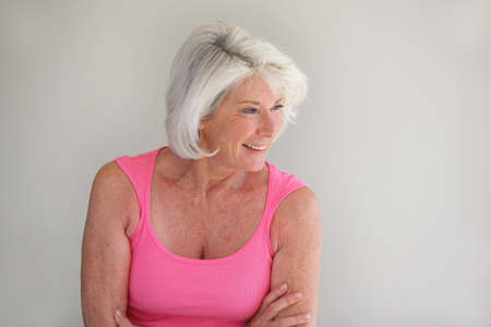 Grey-haired lady posing by wall Stock Photo