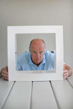 Senior man looking through a frame photo