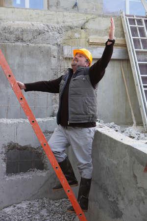 climbing ladder: Builder stood by ladder waving