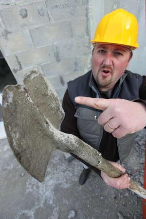 stonemasonry: Tradesman pointing to a worn out spade Stock Photo