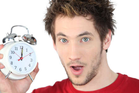 oversleep: Shocked man with alarm clock