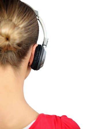 listening back: Girl listening to music with headphones, back view