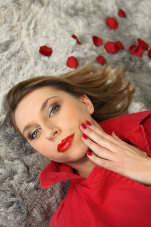 Woman lying surrounded by rose petals photo