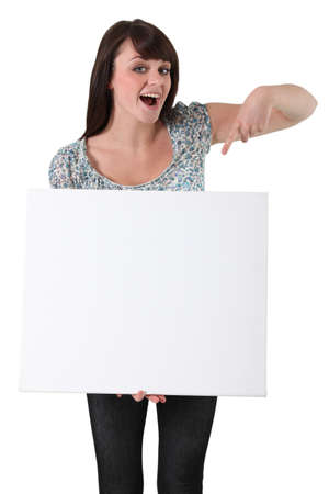 young woman pointing at a blank board photo