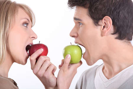 Man and woman about to bite into apples photo