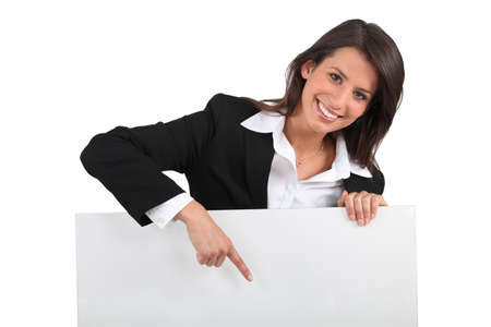 merchandiser: Businesswoman pointing at sign Stock Photo