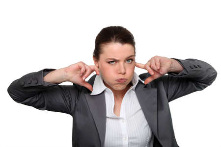 hysterics: Brunette office worker with fingers in ears Stock Photo