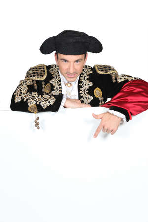 Man in a matador costume with a board blank for text or image photo