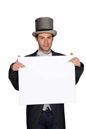 Man in a top hat and tails holding a board left blank for your message Stock Photo - 14106334