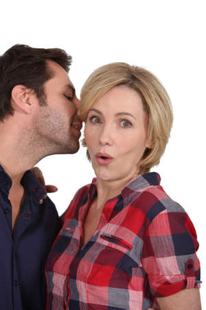 Man talking to womans ear photo