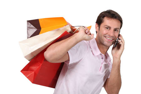 Man using a cellphone with bags of shopping Stock Photo