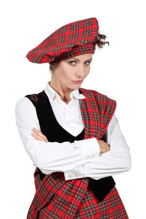 unsatisfied: unsatisfied woman crossing arms and wearing Scottish clothes Stock Photo