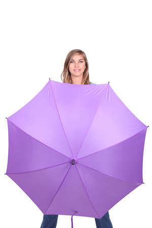 gusty: Young woman posing with an open umbrella in bright purple Stock Photo