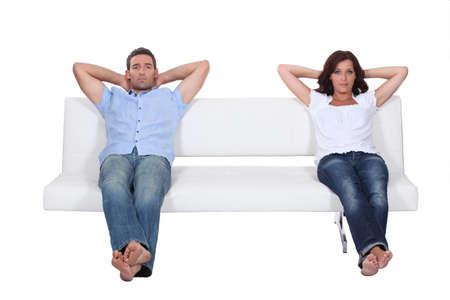 bored man: Coppia, seduta sul divano bianco Archivio Fotografico