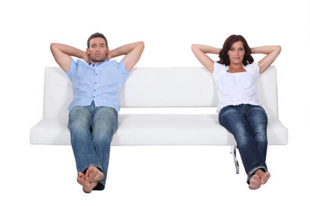 bored woman: Couple sitting on white sofa