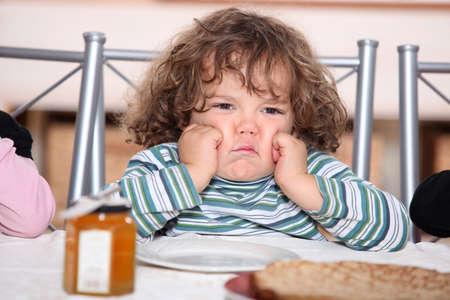 child crying: niño refunfuñando frente a un plato de crepes Foto de archivo